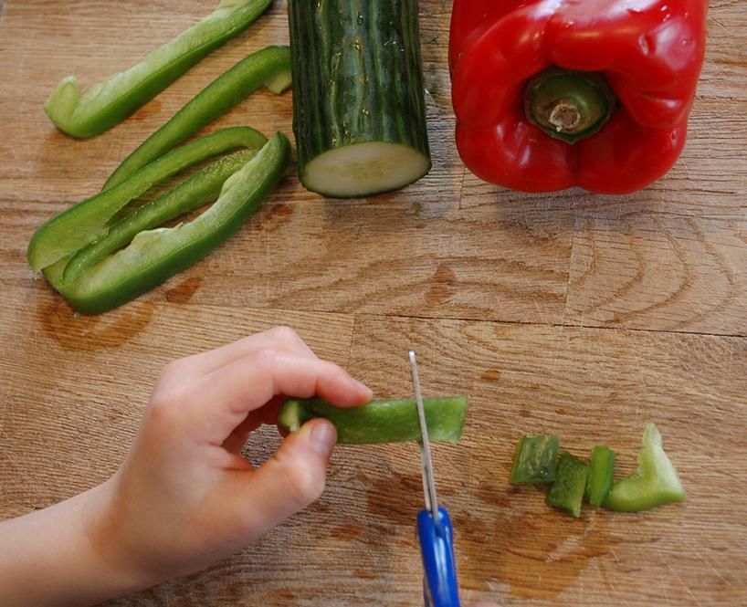 Petites mains qui coupent des lanières de poivron