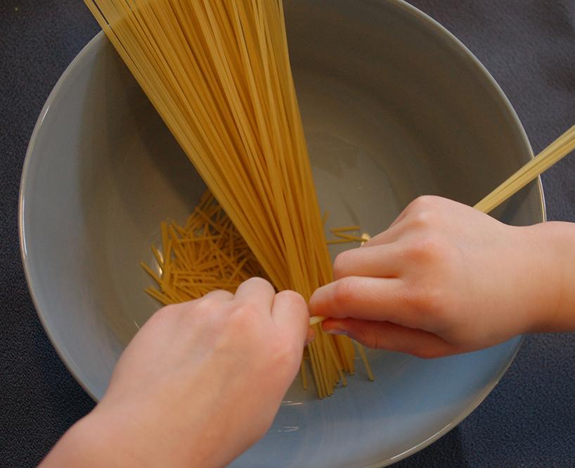 Petites mains qui cassent des nouilles spaghetti en segments de 3cm